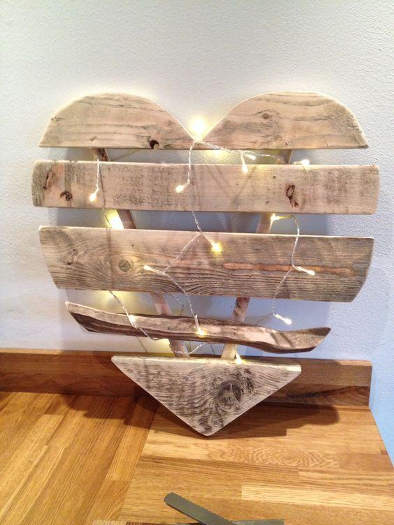 Coração feito com tábuas de madeira e iluminação.