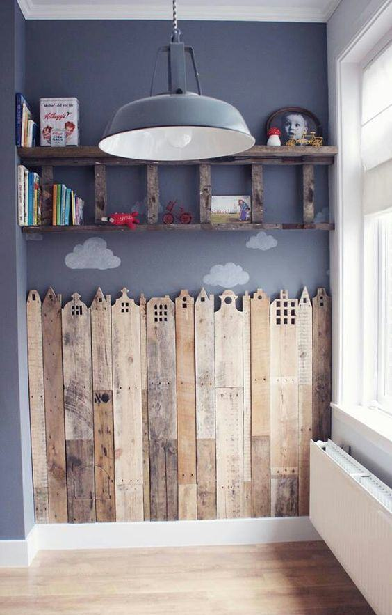 Ao invés do papel de parede, optou-se por colocar madeiras com furos que lembram prédios e construções.
