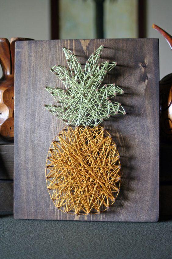 Quadro decorativo com barbantes em formato de abacaxi fixados por pregos.