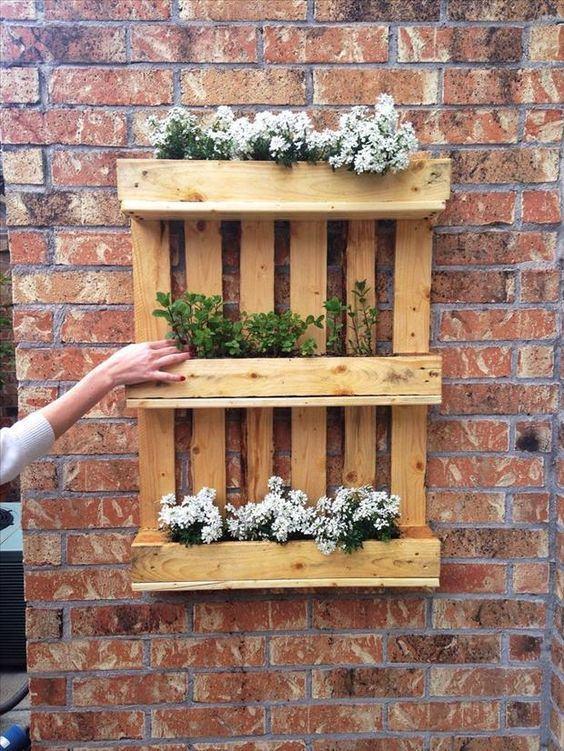 Suporte feito com caixotes para fazer um jardim suspenso.