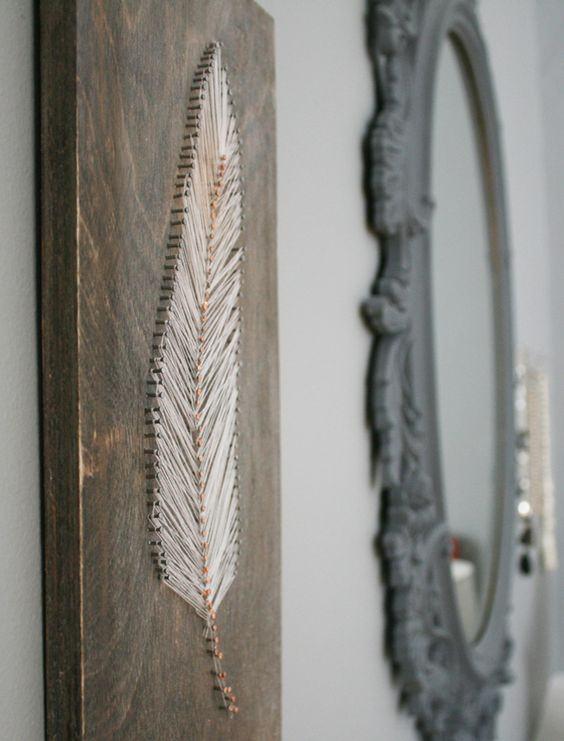 Objeto decorativo de madeira com pena e pregos.