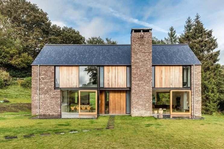 Sobrado de casa de campo com tijolos e detalhes em madeira.