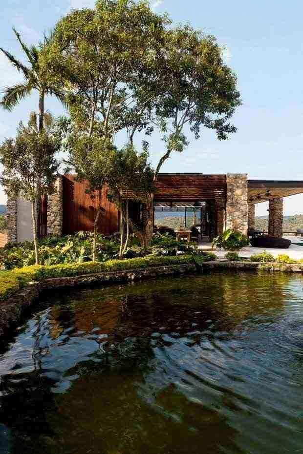 Casa de campo com lago com detalhes de pedra na fachada.