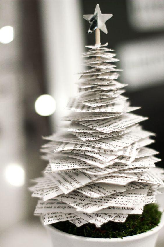 Pequena árvore de Natal simples feita com pedaços de jornal fixados a um palito com estrela brilhante no topo