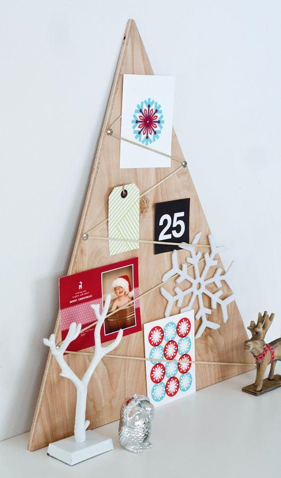 Madeira triangular remete a árvore de Natal com objetos decorativos ao redor
