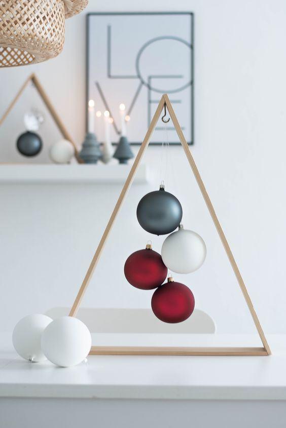 Decoração minimalista com triângulo de madeira fina e bolas de Natal no centro