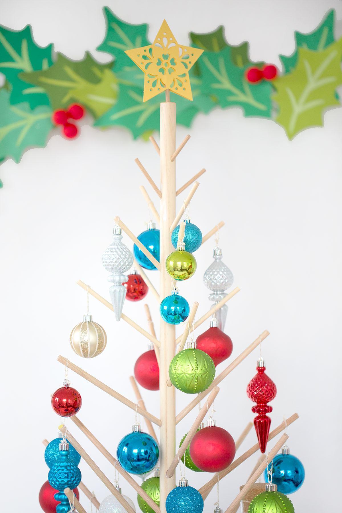 Árvore de Natal de madeira clara com estrela amarela e bolinhas coloridas penduradas