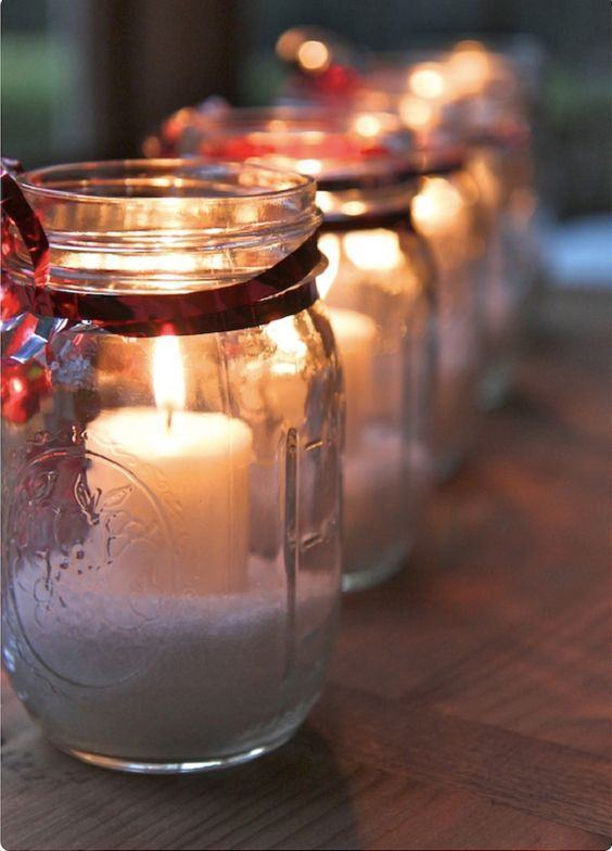 Potes de vidro para abrigar as velas da mesa com fita colorida em volta