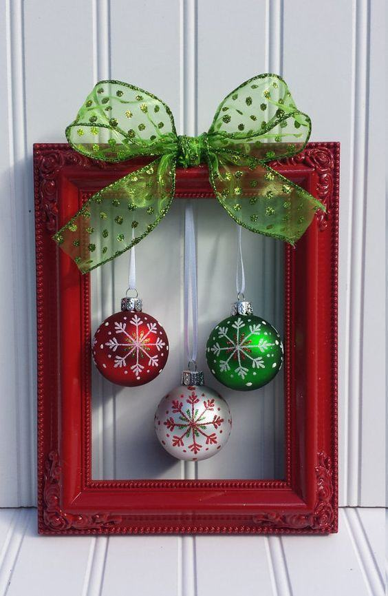 Enfeite feito com moldura de quadro pintada na cor vermelha, laço verde e bolas de Natal coloridas penduradas