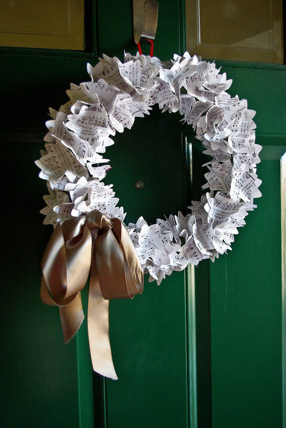 Guirlanda de Natal feita com pedaços de partituras e laço dourado