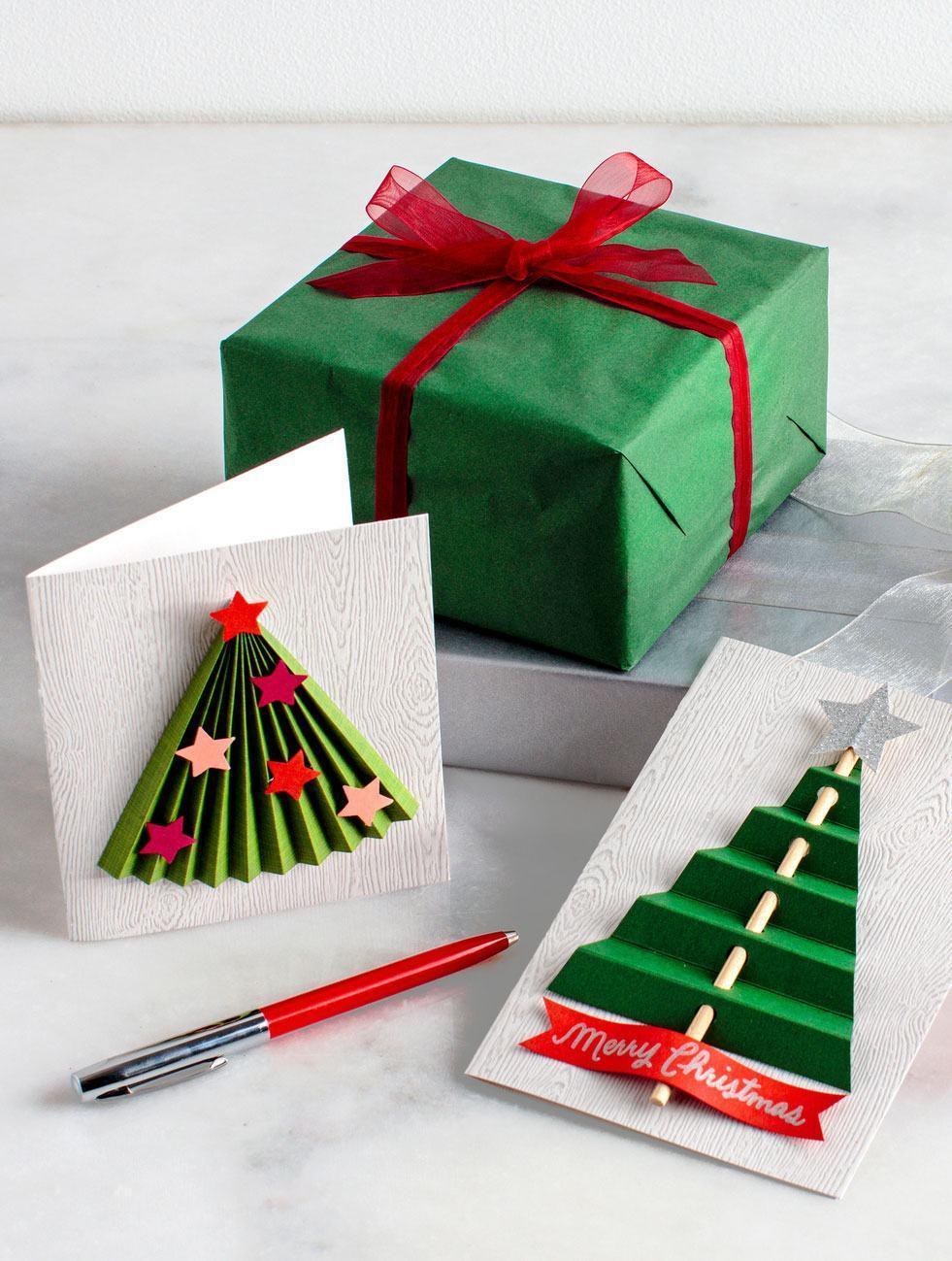 Cartões de natal estilizados com árvores de papel cobradas e coladas junto ao um palito de madeira