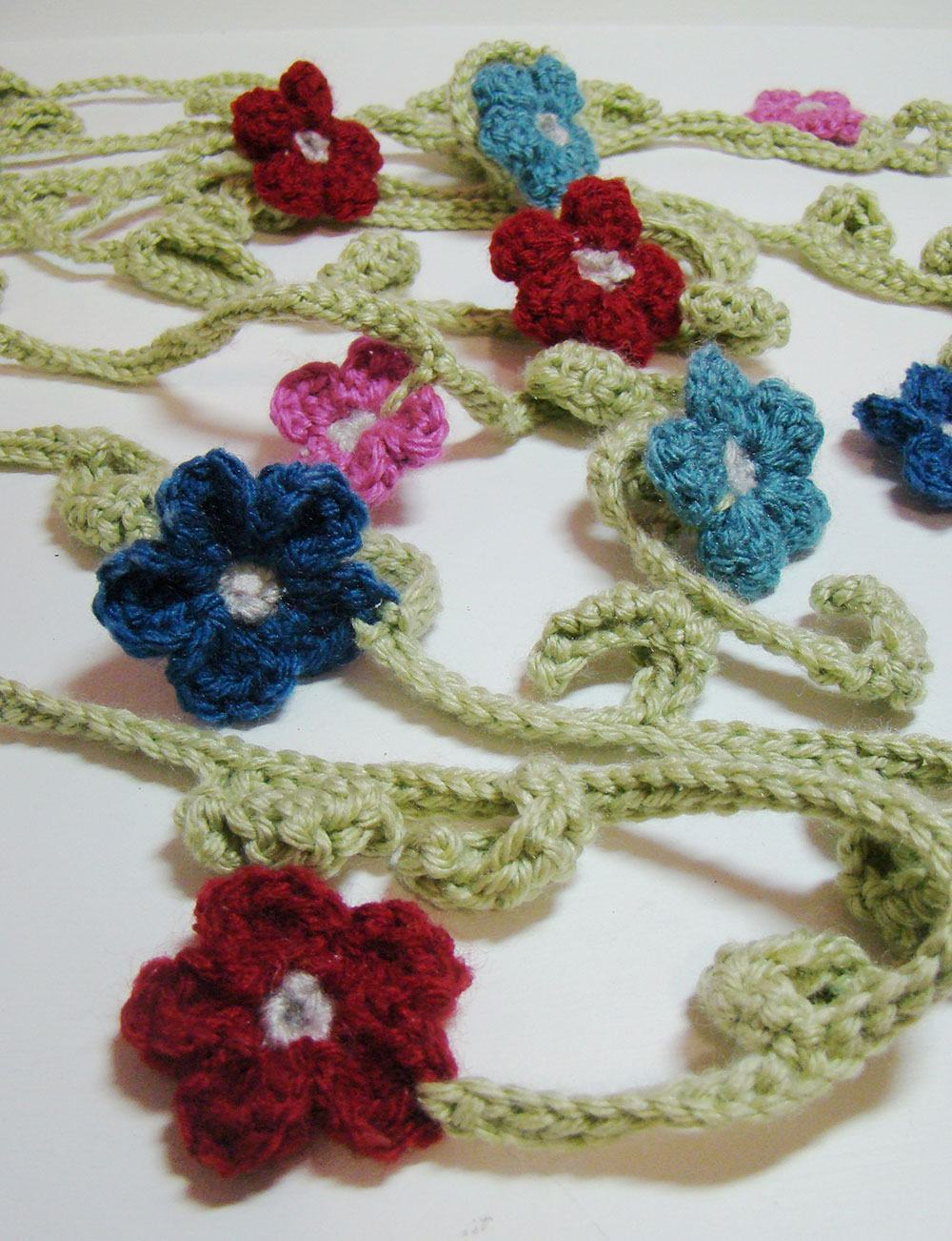 Flores de crochê pequenas unidas por correntinhas