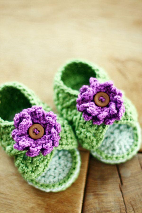 Flor de crochê roxa no sapatinho de bebê