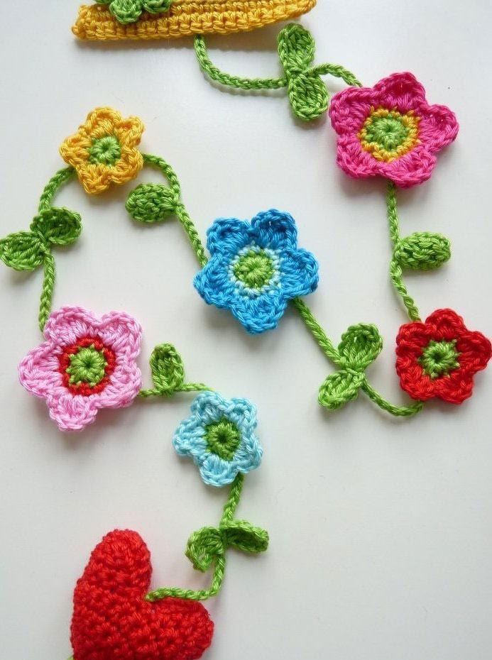 Pequenas flores de crochê unidas por galhos de folhas