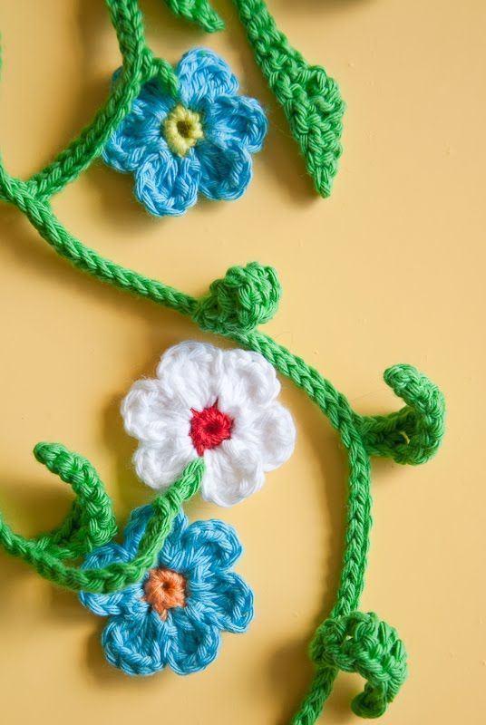 Flores de crochê ligadas por galhos