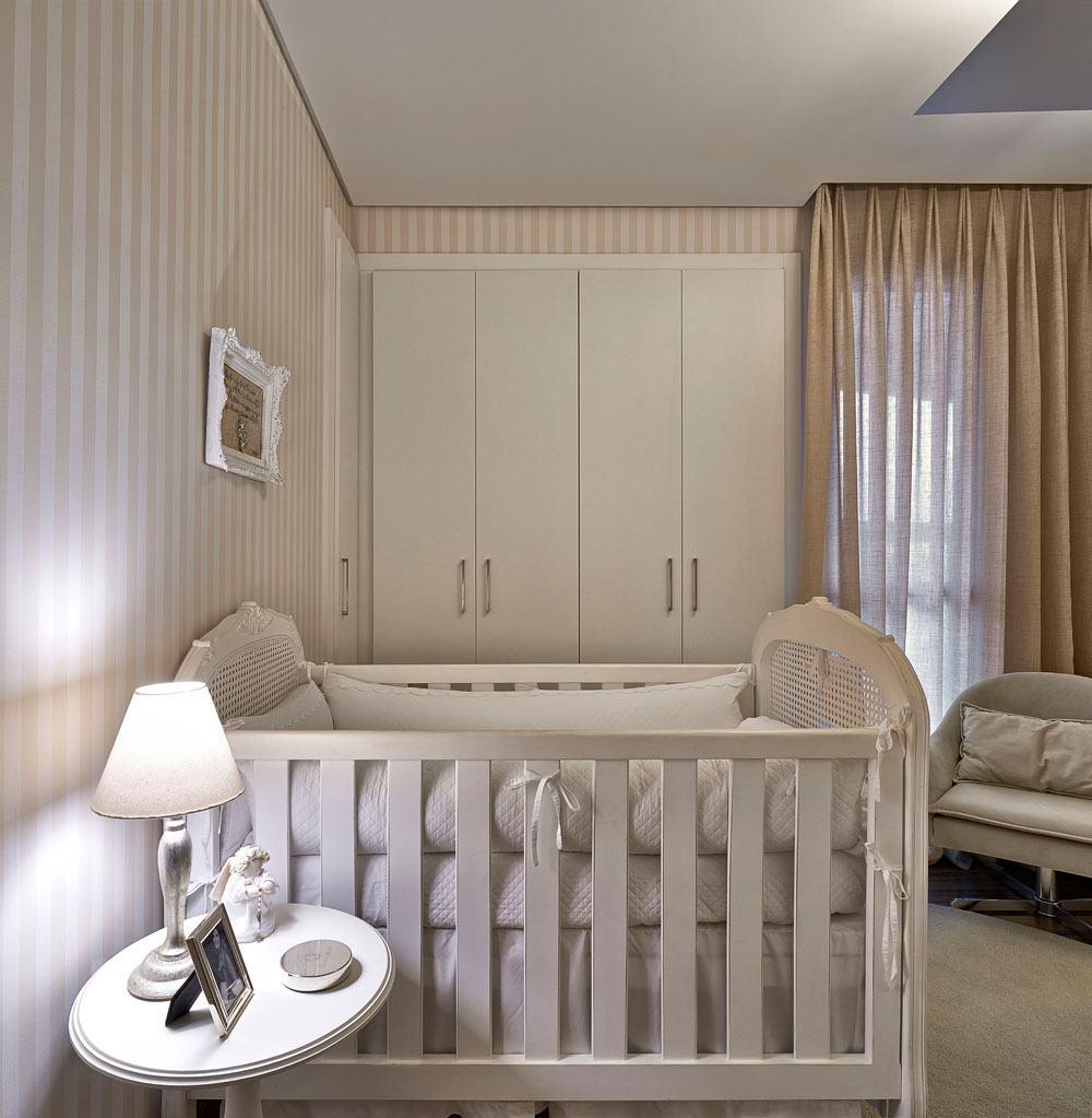 Quarto de bebê com parede listrada bege