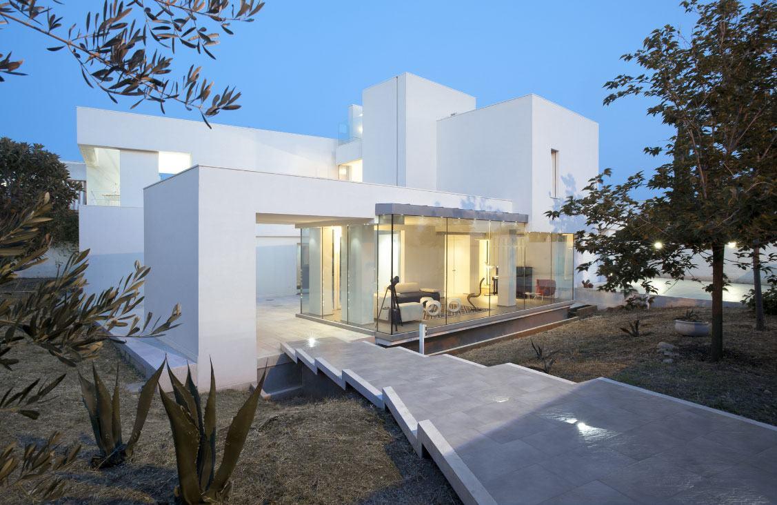 Casa branca com aberturas em vidro