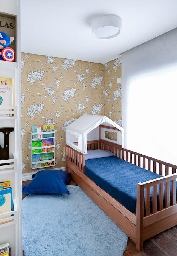 Papel de parede com mapa mundi, cama e tudo organizado neste quarto de menino
