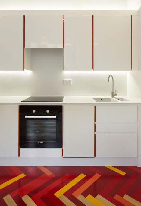 Detalhe para o vermelho nas laterais de portas e gavetas da cozinha, assim como o piso