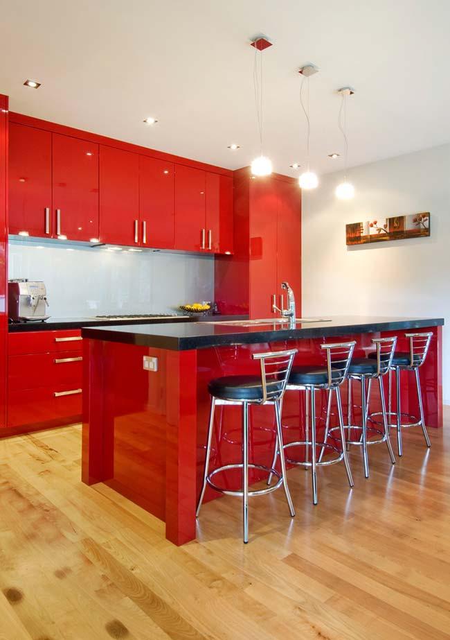Decoração de cozinha com armário e bancada central na cor vermelha