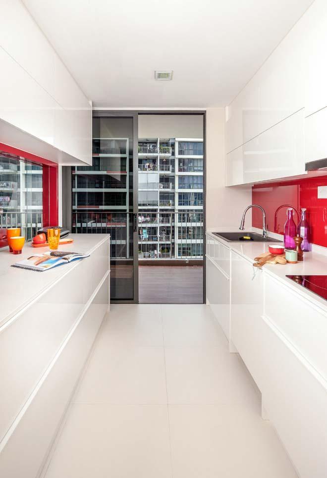 Outro exemplo de cozinha branca onde com o vermelho entre o vão do armário e da bancada