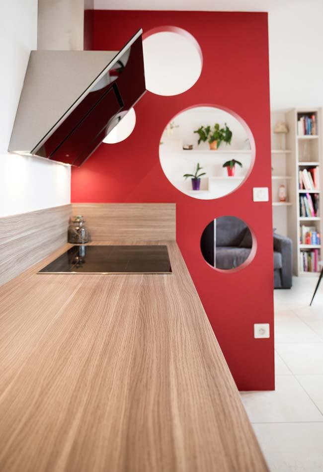 Bancada de madeira na cozinha e parede lateral vazada com a cor vermelha