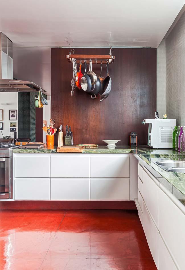 Cimento queimado pintado recebe a cor vermelha no piso desta cozinha