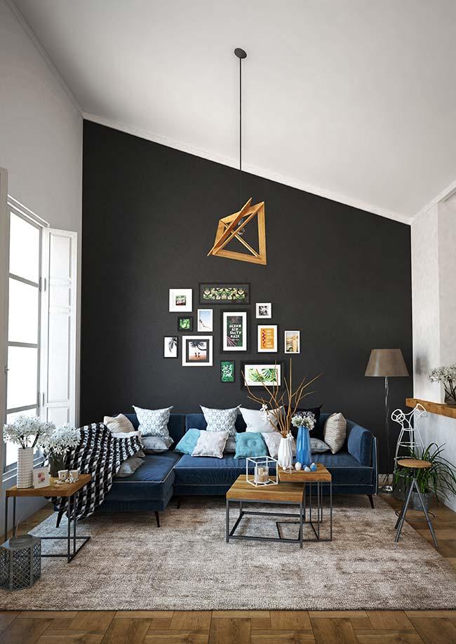 Manta preta e branca faz combinação direto com a parede, mas também se harmoniza com o tom azul do sofá.
