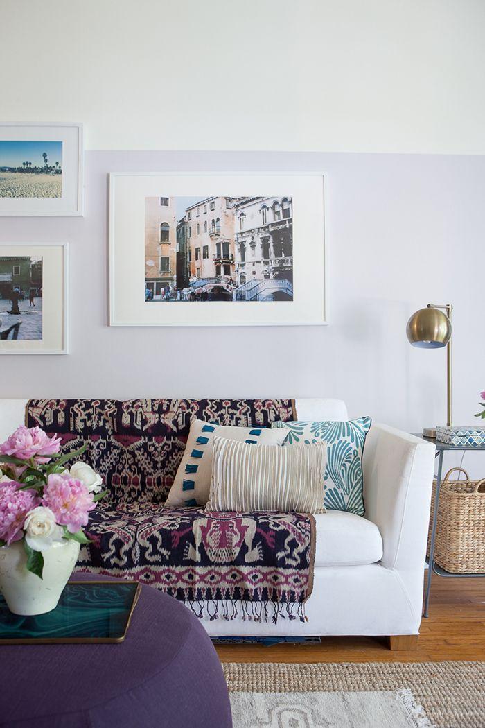 Manta do sofá cheia de cores e estampas conversa com as demais cores da sala