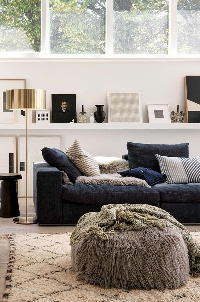 Duas mantas nessa sala: uma sobre o pufe e outra sobre o sofá no mesmo material e cor do pufe