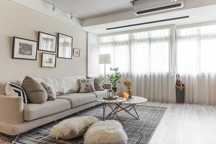Nessa sala, a manta de pele cobre todo o encosto do sofá