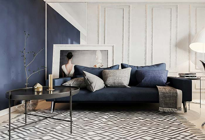 Sobre o belo sofá azul marinho, uma manta com tons de cinza