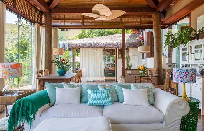 Decoração com ares provençais destaca a manta verde azulada no braço do sofá branco