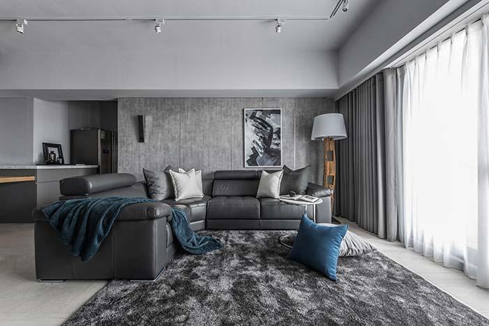 Manta azul forma um contraste sutil com a decoração preta e cinza da sala