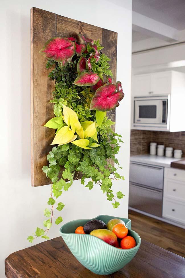 Um quadro vivo e natural de antúrios e hera decora o espaço entre a sala de jantar e a cozinha