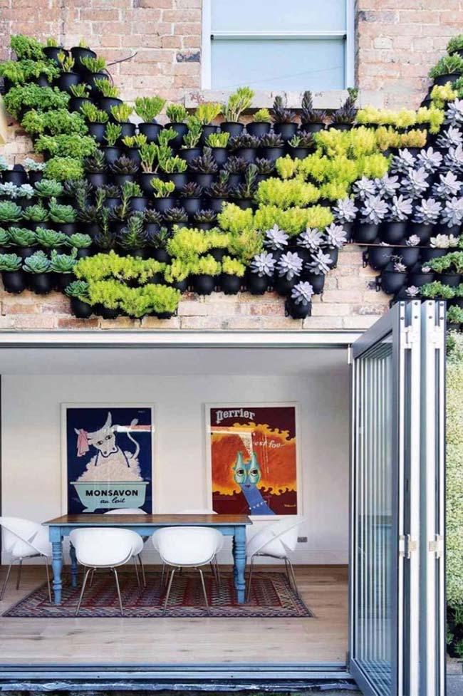 A fachada dessa casa recebeu vasos de cores e espécies variadas para formar o jardim vertical