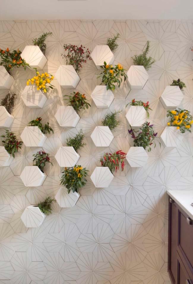 Pimentas e temperos plantados em vasos que se destacam de dentro da parede