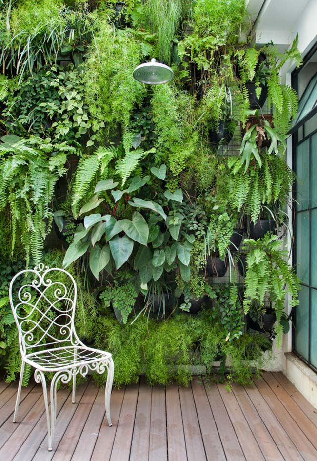 Esse jardim vertical, construído com vasos fixados na tela aramada, é formado por um mix de plantas de meia sombra