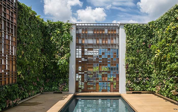 Moldura verde em torno da piscina deixa tanto o ambiente interno, quanto externo mais agradável