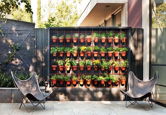 Tela aramada serve de apoio para os vasos de barro com ervas e temperos