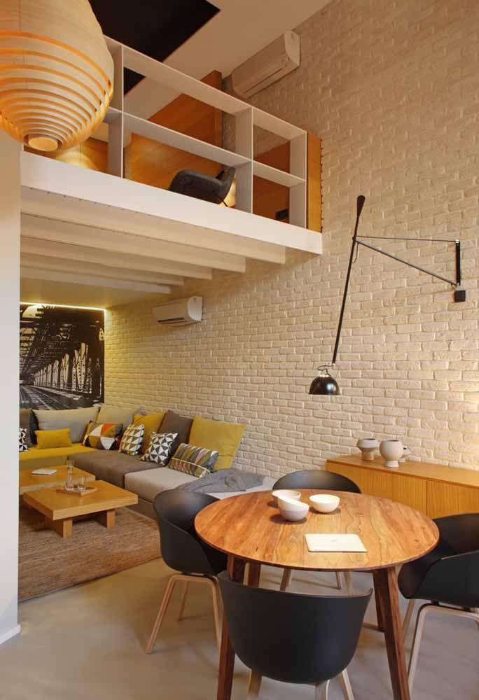 Rústica e moderna, essa casa apostou em um mezanino de madeira branca para acomodar a segunda sala de estar