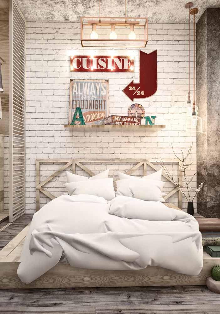 Nesse quarto de casal, o toque vintage na decoração fica por conta da parede de tijolinhos branca, os quadros e o letreiro luminoso