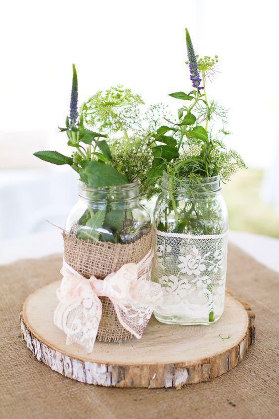Frascos utilizados como vaso decorados com tecido de juta, renda e laço colorido.