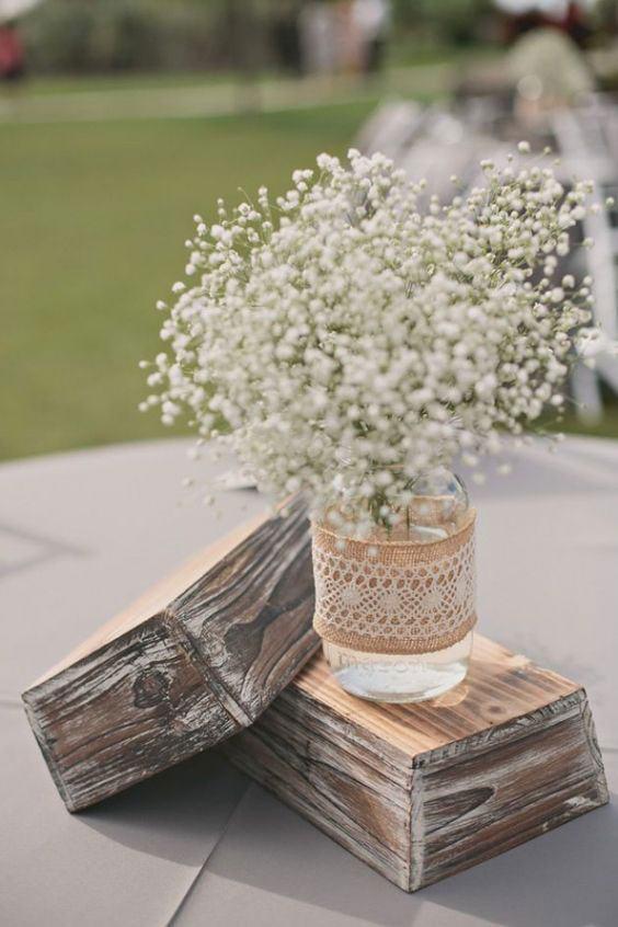Pequeno vaso com frasco de vidro apoiado sob peça de madeira na decoração da mesa