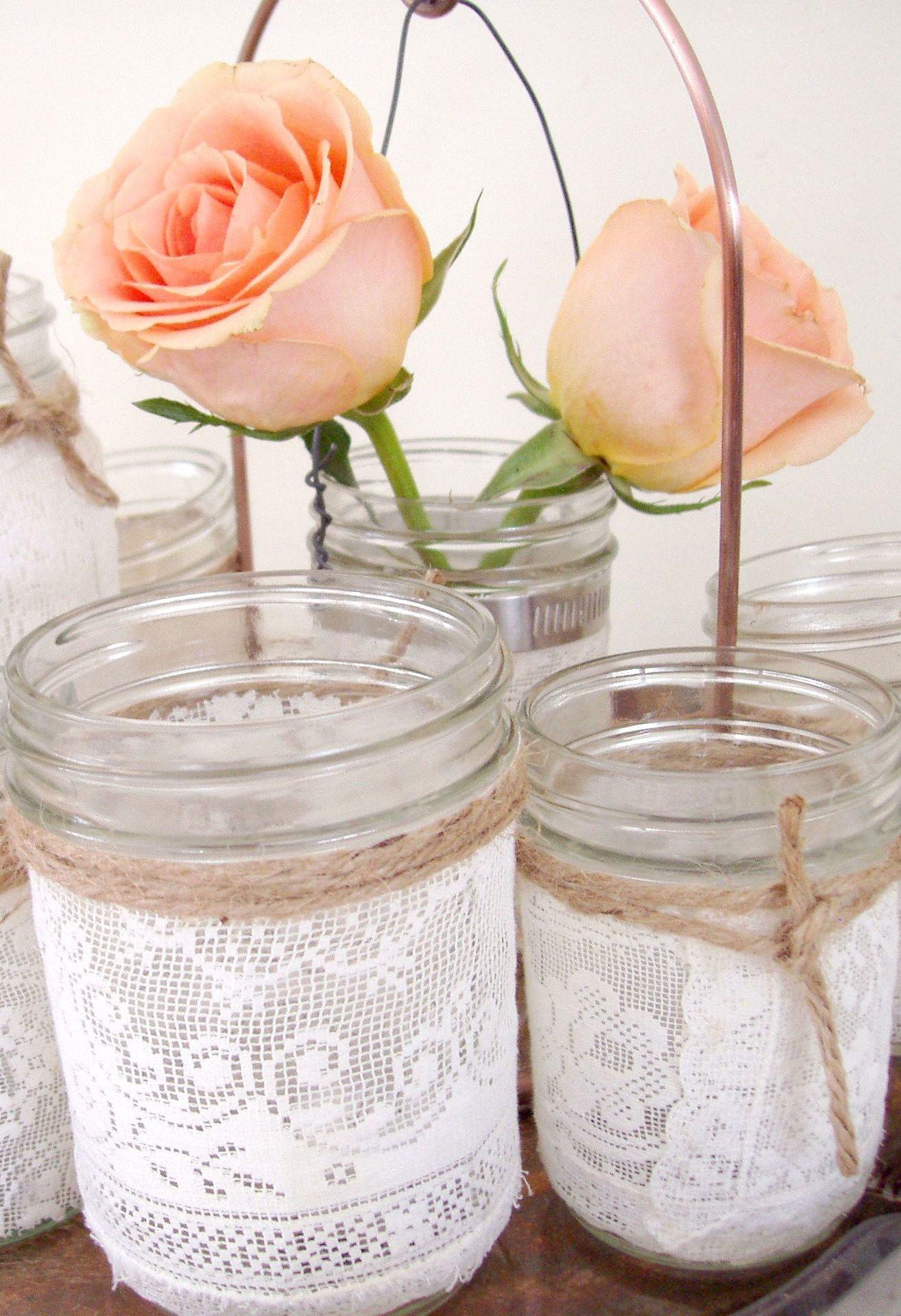 Em um pequeno frasco para abrigar uma vela, agregue com o tecido de renda