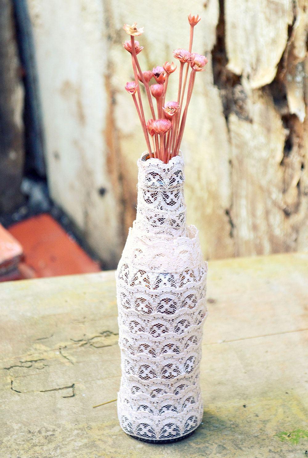 Garrafa como vaso coberta com camadas de tecido de renda