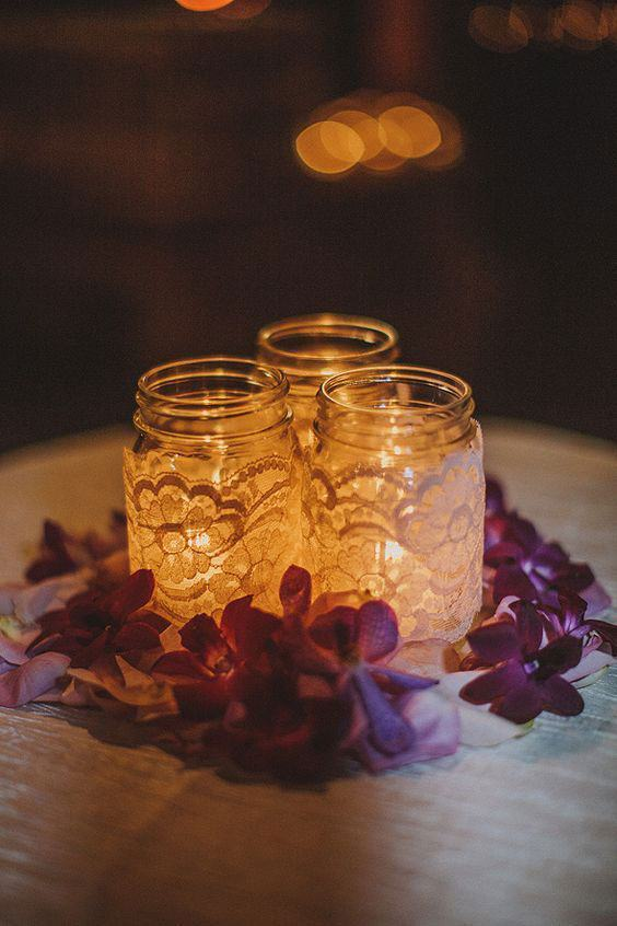 Linda decoração com frascos de vidro com velas e renda