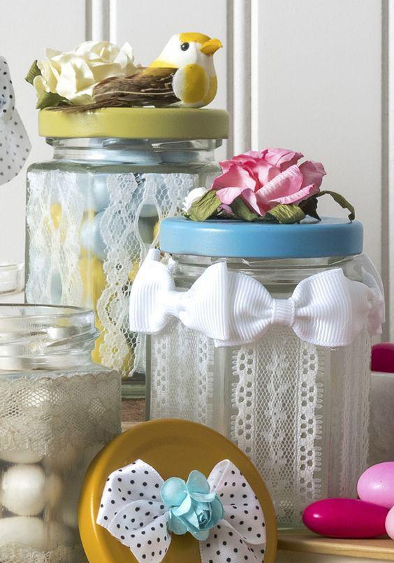 Frascos com tampas coloridas cobertos por renda e laços brancos
