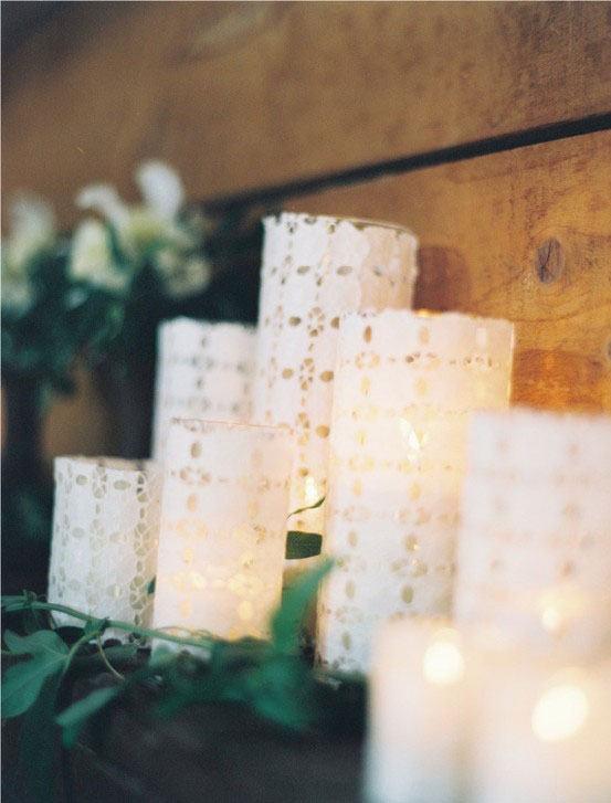 Pequenos frascos com vela cobertos por tecido de renda