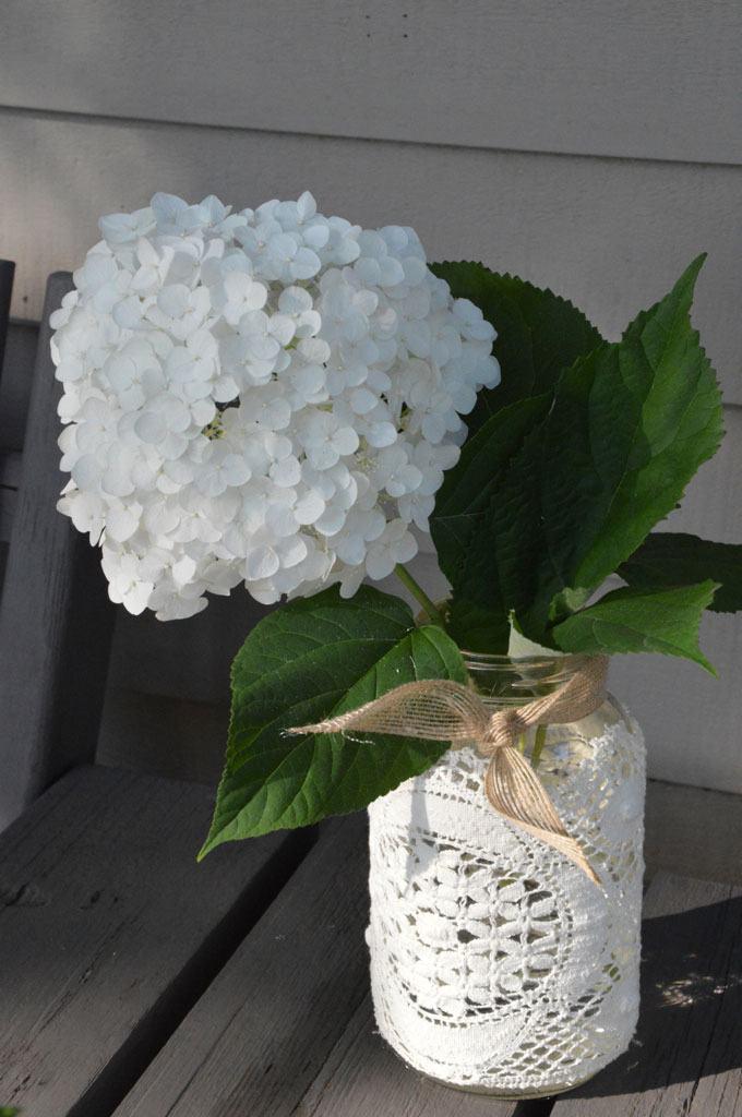 Vaso com tecido de renda e flores